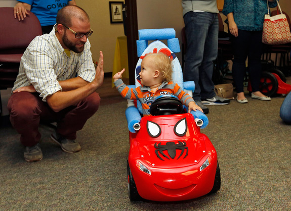 Christopher Roe high-fives Go Baby Go workshop leader Sam Logan in his newly modified Fisher-Price Power Wheels Lil' Lightning McQueen. (Kyle Robertson/Columbus Dispatch/MCT)